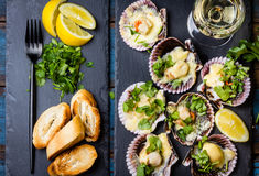 Baked scallops on slate with lemon, cilantro, bread white wine. Seafood. Shellfish. Baked scallops on slate plate with lemon, cilantro, bread and white wine on Royalty Free Stock Photos