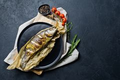 Baked sea bass on Kraft paper in a black plate. Black background, top view, space for text. royalty free stock image