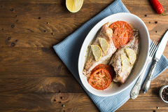 Baked sea bass with tomatoes and lemon. Baked sea bass with tomatoes Stock Image