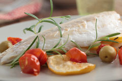 Baked sea bass with vegetables. Baked sea bass with cherry tomato, olives, and rosemary Stock Image