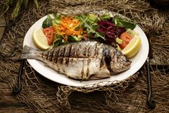 Baked sea bream and salad by royalty free stock photos