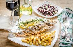 Baked seabass with fried potatoes Royalty Free Stock Images