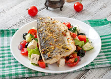 Baked seabass with Greek salad Royalty Free Stock Photo