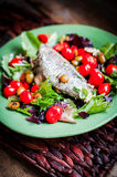 Baked seabass with tomatoes and basil on rustic wooden backgroun Royalty Free Stock Photo