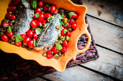 Baked seabass with tomatoes and basil on rustic wooden backgroun Stock Photography