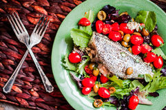 Baked seabass with tomatoes and basil on rustic wooden backgroun Stock Photos