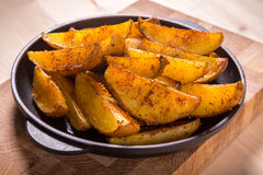 Baked sliced potatoes on pan Royalty Free Stock Photo