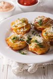 Baked sliced potatoes with Parmesan close-up on a plate. Vertica Stock Images