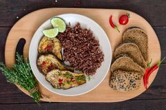 Baked slices of eggplant, butane red rice with rye bread with sesame and poppy seeds. Royalty Free Stock Images