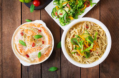 Baked slices of red and white fish with honey and lime juice, served with fresh salad and soft noodles in miso broth. Royalty Free Stock Photos