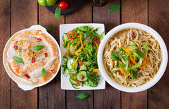 Baked slices of red and white fish with honey and lime juice, served with fresh salad and soft noodles in miso broth. Royalty Free Stock Photo