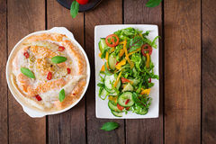 Baked slices of red and white fish with honey and lime juice, served with fresh salad. Stock Photo