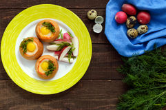 Baked small flavorful bun with bacon, cheese, quail egg and greens. Tasty breakfast. The top view Stock Photo