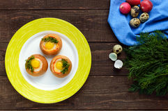 Baked small flavorful bun with bacon, cheese, quail egg. And greens. Tasty breakfast. The top view Stock Photos