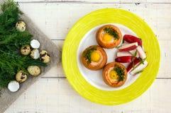 Baked small flavorful bun with bacon, cheese, quail egg Stock Photos