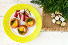 Baked small flavorful bun with bacon, cheese, quail egg. And greens. Tasty breakfast. The top view Stock Images