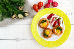 Baked small flavorful bun with bacon, cheese, quail egg and greens. Tasty breakfast. The top view Stock Images