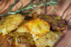 Baked smashed potatoes. Serving of potatoes that have been smashed and then baked with seasoned oil and spices as a side dish Royalty Free Stock Image