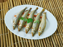 Baked smelt. Served with roasted carrots Royalty Free Stock Photos