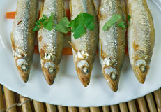 Baked smelt. Served with roasted carrots Royalty Free Stock Images
