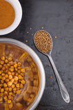 Baked spiced chickpeas in metal bowl, paprika and coriander seeds on black surface Stock Image