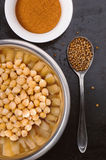 Baked spiced chickpeas in metal bowl, paprika and coriander seeds on black surface Stock Photos