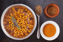 Baked spiced chickpeas in metal bowl, paprika Stock Photo