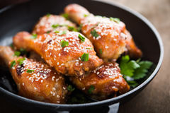 Baked spicy chicken legs with sesame and parsley in cast iron frying pan on dark wooden background Stock Photo
