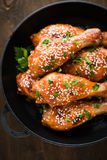 Baked spicy chicken legs with sesame and parsley in cast iron frying pan on dark wooden background Stock Photos