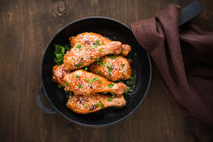 Baked spicy chicken legs with sesame and parsley in cast iron frying pan on dark wooden background. Top view Royalty Free Stock Image