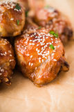 Baked spicy chicken legs with sesame and parsley on paper background. Close up Royalty Free Stock Photography