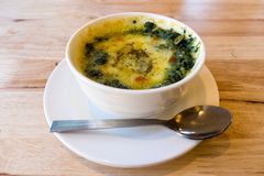 Baked Spinach with Cheese. In white cup on the table Royalty Free Stock Photo