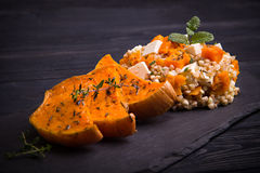 Baked squah salad with feta cheese on black slate plate Stock Photo