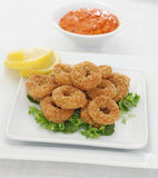 Baked squid rings. Calamari with sweet pepper dip Royalty Free Stock Photos