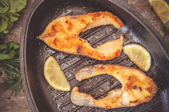 Baked steak trout fish in cast-iron form, around greens, leaves, lettuce, lemon, olive oil, pepper, condiments. From above, close. Up. Concept of healthy eating stock photography