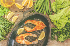 Baked steak trout fish in cast-iron form, around greens, leaves, lettuce, lemon, olive oil, pepper, condiments. From above, close. Up. Concept of healthy eating stock image