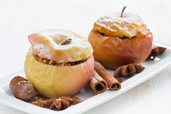 Baked stuffed apples on a plate on white wooden table, close-up Stock Photo
