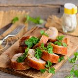 Baked stuffed chicken rolls on a wooden board. Fork, knife, salt shaker, parsley on a wooden table. Rustic style Royalty Free Stock Photography