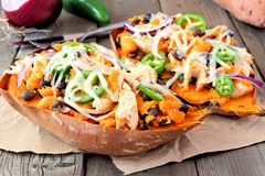 Baked, stuffed sweet potatoes, close up against rustic wood Royalty Free Stock Images