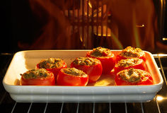 Baked stuffed tomatoes in the oven Stock Image