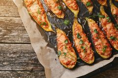 Baked stuffed zucchini with meat in a pan on wooden boards. Royalty Free Stock Photos