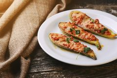 Baked stuffed zucchini with meat on a plate. Stock Image