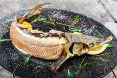 Baked sturgeon fish with rosemary, lemon and passion fruit on plate on wooden background close up stock images