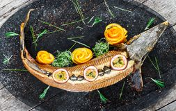 Baked sturgeon fish with rosemary, lemon and passion fruit on plate on wooden background close up stock photos