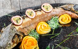 Baked sturgeon fish with rosemary, lemon and passion fruit on plate on wooden background close up. stock photos
