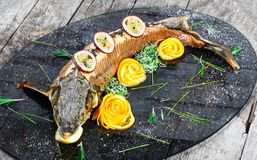 Baked sturgeon fish with rosemary, lemon and passion fruit on plate on wooden background close up. stock images