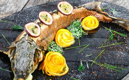 Baked sturgeon fish with rosemary, lemon and passion fruit on plate on wooden background close up stock photography