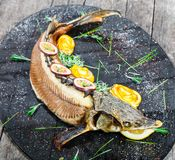 Baked sturgeon fish with rosemary, lemon and passion fruit on plate on wooden background close up. royalty free stock image