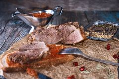 Baked succulent pork meat, sliced pieces on parchment paper, close-up with bread and tomato sauce, dark wooden rustic background royalty free stock image