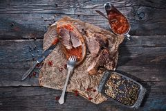 Baked succulent pork meat, sliced pieces on parchment paper, close-up with bread and tomato sauce, dark wooden rustic background royalty free stock photo